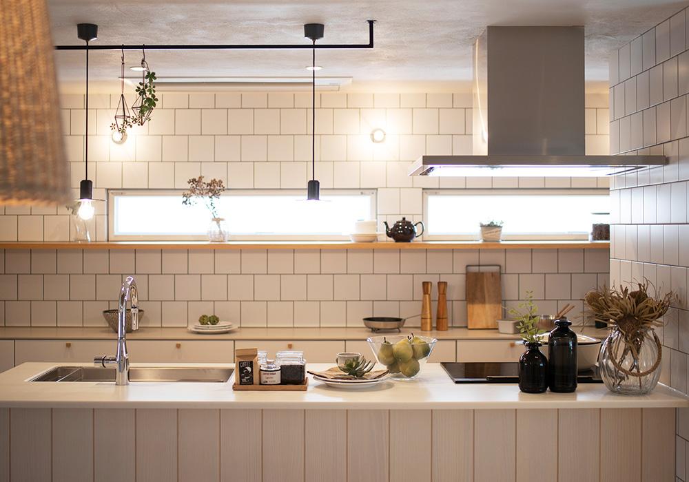 白いタイルと白の板張りがナチュラルなキッチン。タイルの黒目地とアイアン照明が、明るくナチュラルなテイストに程よいアクセントを与えます。