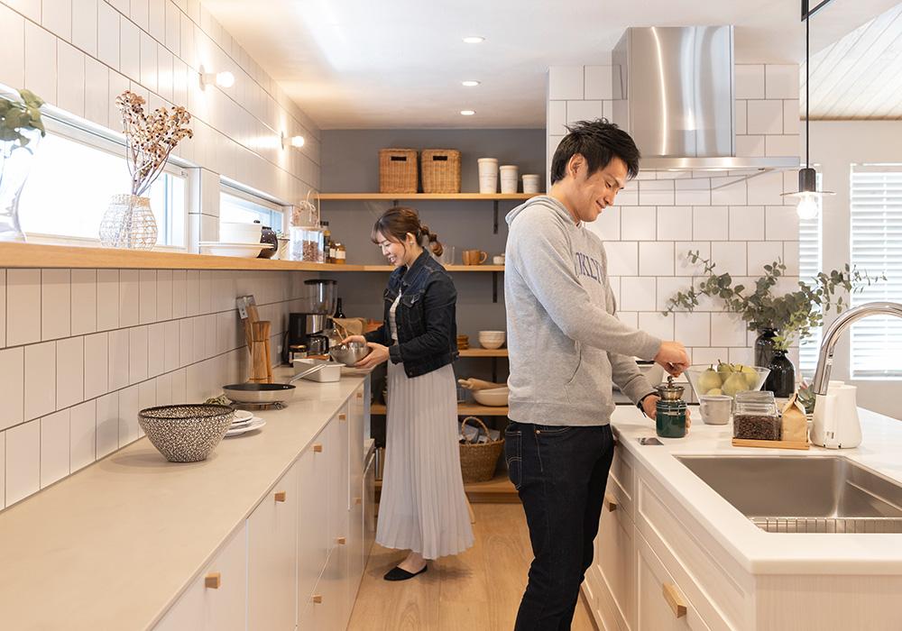 2人で並んでもゆとりある広さのキッチンは、タイルと収納を白で統一した清潔感のある優しい雰囲気に仕上げました。キッチン奥のパントリーは冷蔵庫を隠せるのですっきりとした印象に。