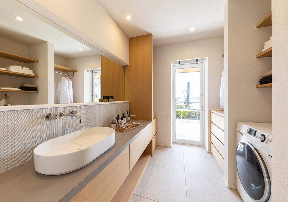 家族が並んで身支度ができるワイドサイズの洗面台がある脱衣室。横幅いっぱいのミラーが広々空間を演出します。洗濯物を干してしまうまでをその場で完結できる家事動線が◎