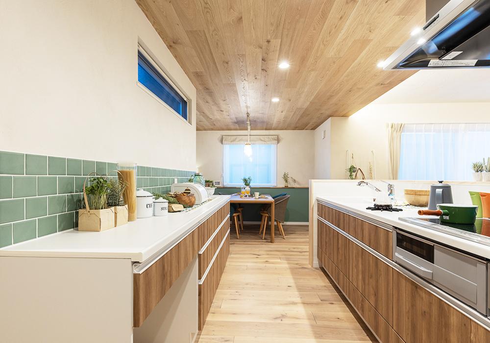 木のぬくもりを感じる、板張り天井のダイニングキッチン。爽やかなグリーンのタイルで気分がリフレッシュされ、料理の時間が楽しくなります。