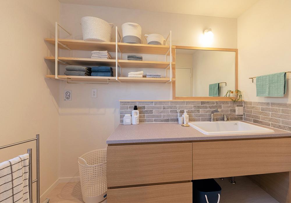 木枠のミラーとタイルがお洒落な造作洗面台は、洗濯物を畳める程の広さがあります。また、メイクやヘアセットものびのびとできるので身支度が楽しくなりそうです。