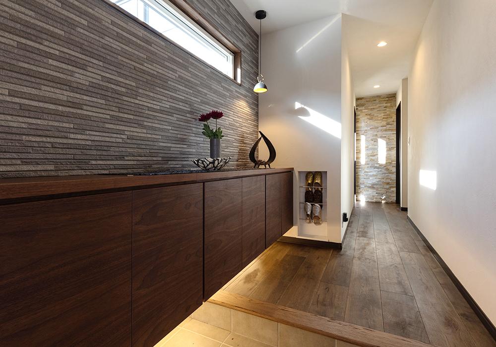 ストーンタイル×間接照明でシックに仕上げた玄関。壁に埋め込まれたスリッパラックは、場所を取らずスッキリと見せてくれます。造作収納には靴をたっぷり収納できるので、急な来客時も安心です。